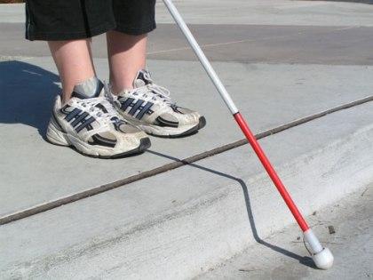 Photo of a blind pedestrian navigating a curb