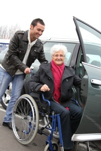 Photo of elderly person being helped into a vehicle