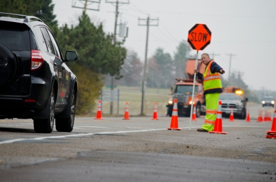 Work-zone flagger holding a stop sign up for cars as they approach a construction zone
