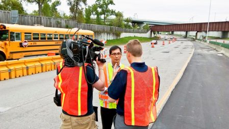 KARE 11 reporters interviewing researcher Chen-Fu Liao next to a highway work zone.