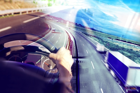 Driver at the steering wheel of a semi truck, with a view of the freeway through the windshield